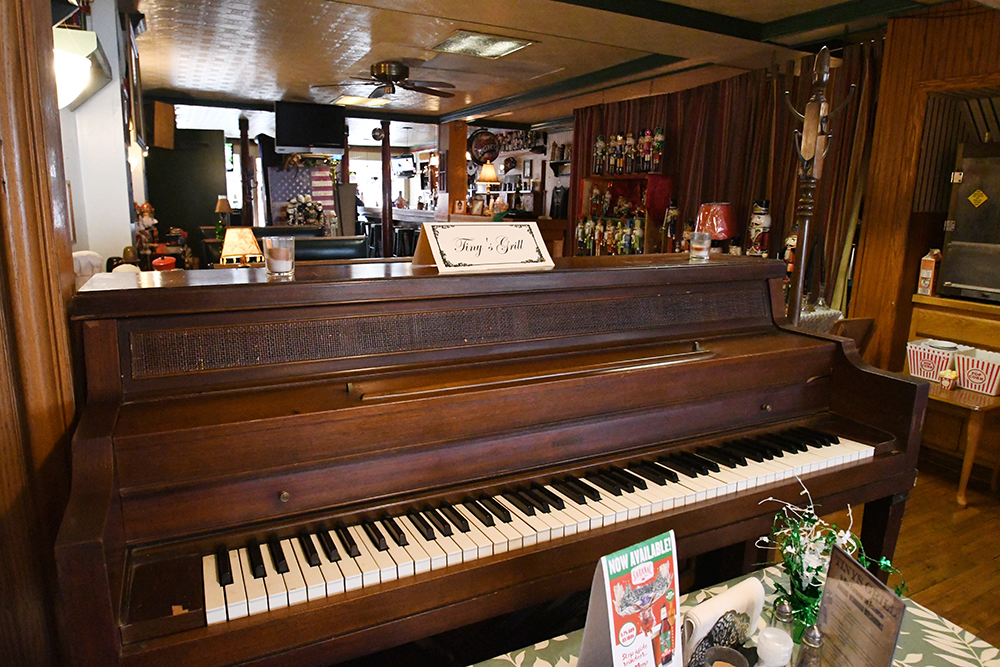 "Piano with ""Tiny's Grill"" tent card, restaurant and bar in background"