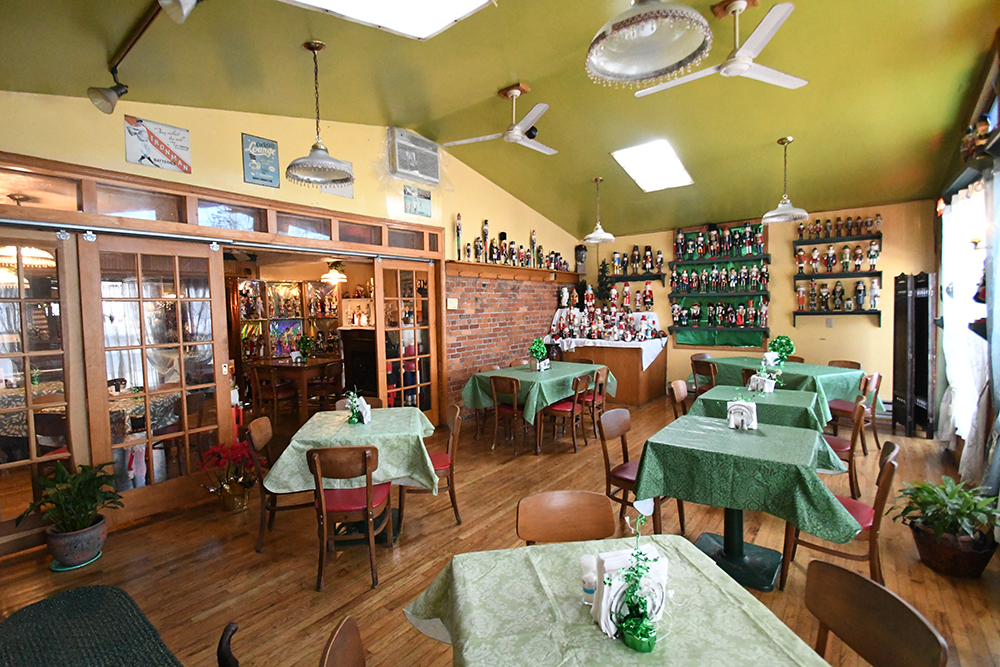 Back sun room at Tiny's with tables, Saint Patrick's Day decorations, and part of nutcracker collection