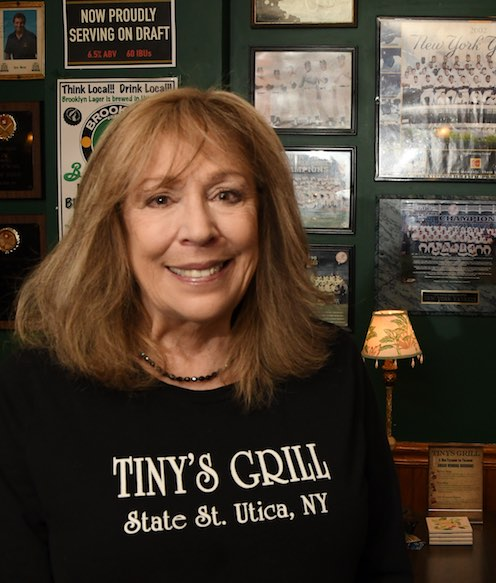 Joanne Gerace smiling in front of sports memorabilia photos on wall inside Tiny's Grill