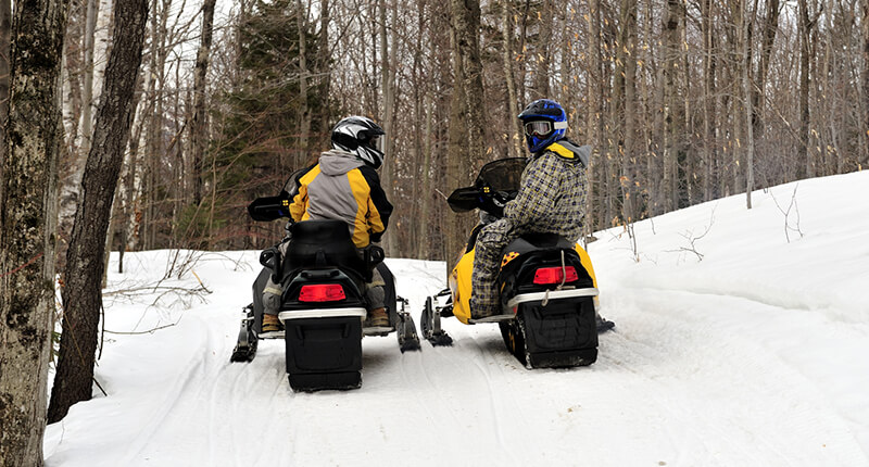 Snowmobilers on a trail in the Adirondacks stop briefly to plan their route