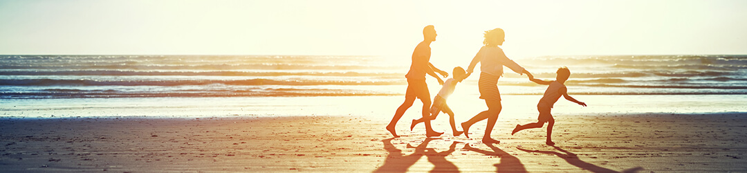 Family runs along ocean beach at sunset while on vacation paid for with a loan