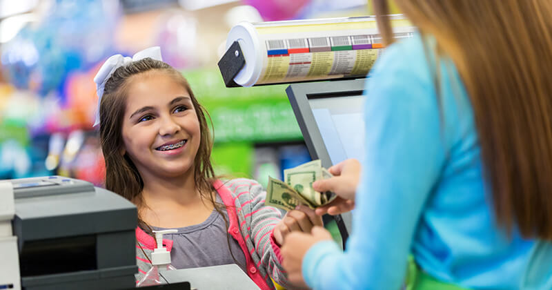 Young girl making a purchase and learning the importance of money