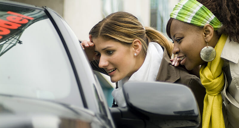 Young women look in the window of a new car after applying for an Auto Loan.